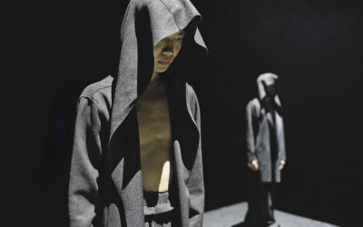 Two dancers standing on stage in hooded cloaks