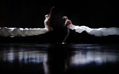 Two dancers stand back to back with fabric billowing around them