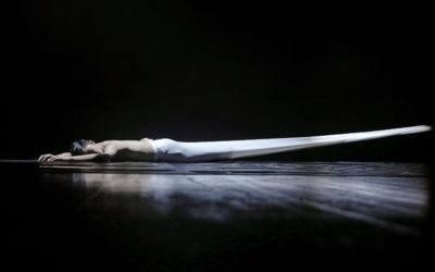 One dancer lays on stage wrapped in a piece of fabric