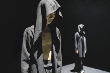 Two dancers wear hooded cloaks