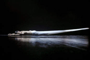 A dancer lays on the floor